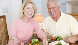 woman with senior man smiling while eating