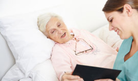 senior woman with female caregiver looking something on document