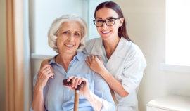 female caregiver hugs senior woman