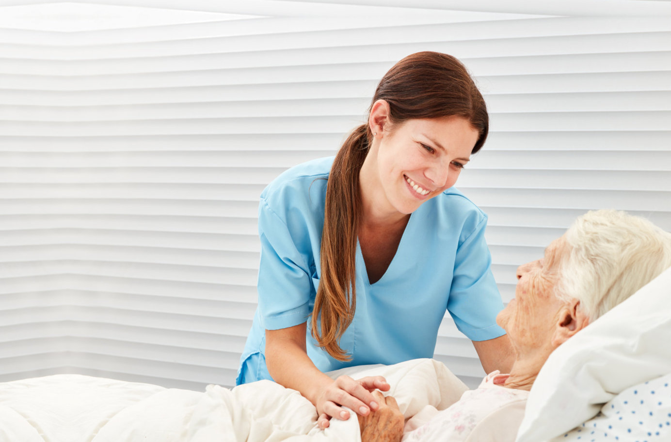 female caregiver taking care of senior woman in bed
