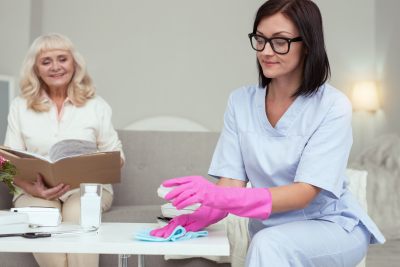 caregiver cleaning the table while the senior woman is reading a book