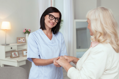 caregiver and senior woman are smiling while holding hands together