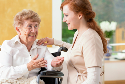smiling senior woman talking to a friendly caregiver