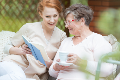 caregiver reading the book while senior woman is listening at the garden