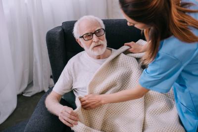 caregiver covering senior man with plaid
