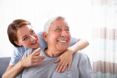 caregiver and senior man are smiling while taking a picture