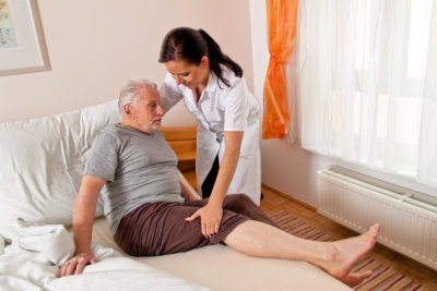 caregiver assisting her patient to bed