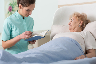 caregiver reading the booking while the ill senior woman listening