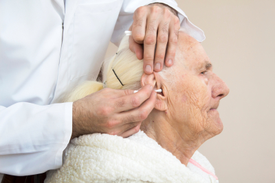caregiver cleaning the ears of an senior woman using cotton swabs